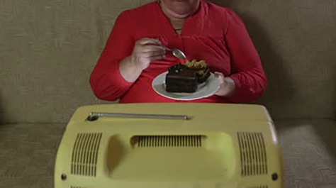 stock-footage-overweight-woman-eating-cake-and-watching-vintage-tv